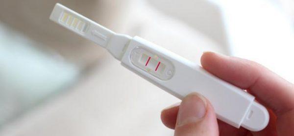 Рука держит тест на беременность с двумя полосками