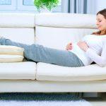 Беременная лежит на диване, положив ноги на подушки