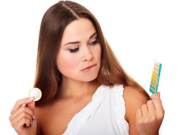 Девушка держит в руке презерватив и противозачаточные таблетки