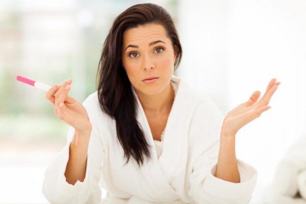 Девушка разводит руками, в одной тест на беременность