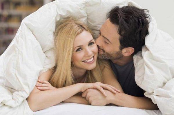 Парень целует девушку под одеялом