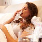 Женщина лежит в постели и вытирает нос платком