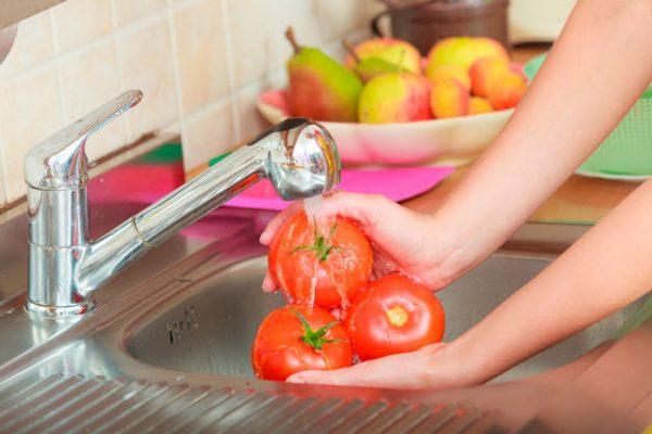 Женщина моет помидоры