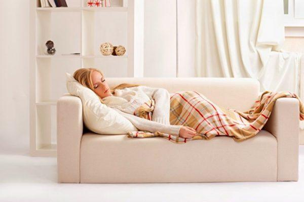 Женщина отдыхает лёжа на диване