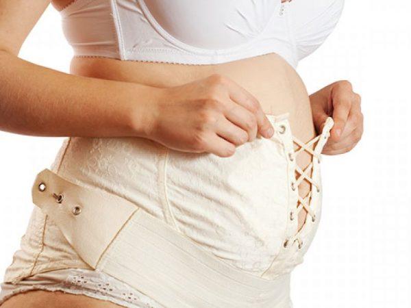 Беременная надевает бандаж
