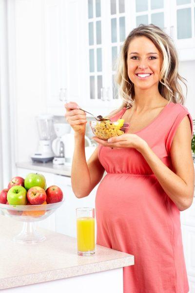 беременная с тарелкой мюсли стоит рядом с яблоками и соком