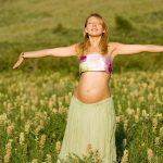 Беременная женщина стоит, раскинув руки, на лугу в солнечную погоду