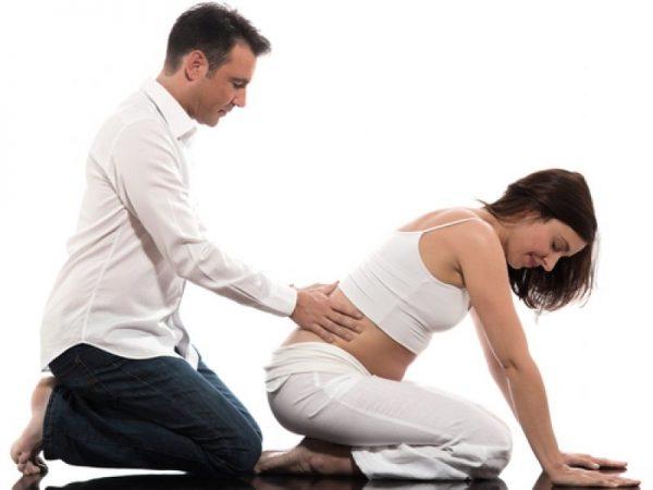 Специалист делает массаж спины беременной