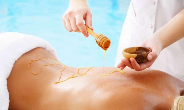 Женщине наносят мёд на спину