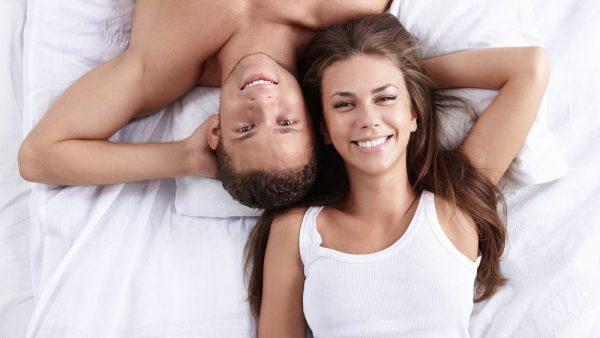 Мужчина и женщина лежат на кровати и улыбаются