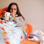 Простуженная женщина лежит в постели