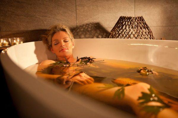 Женщина принимает ванну с ламинарией