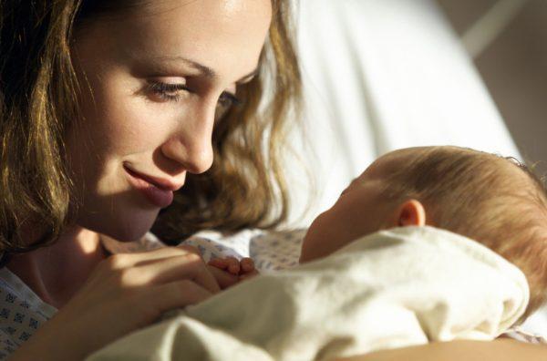 Мама держит грудного ребенка и улыбается