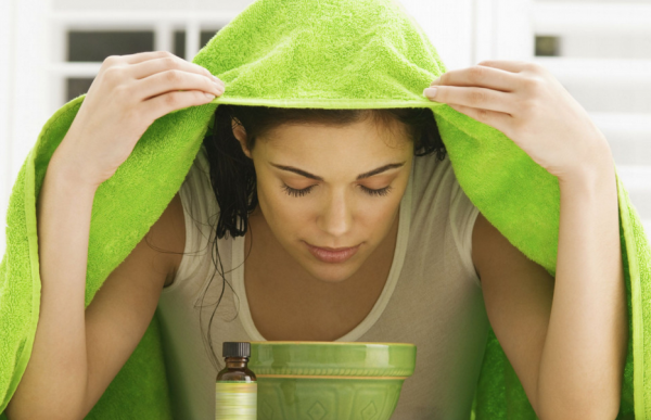 Женщина дышит над чашкой с раствором эфирного масла
