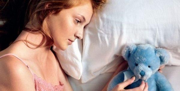 Женщина смотрит на игрушку и переживает