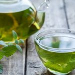 Чай с мятой и мелиссой в прозрачных чайнике и кружке на столе