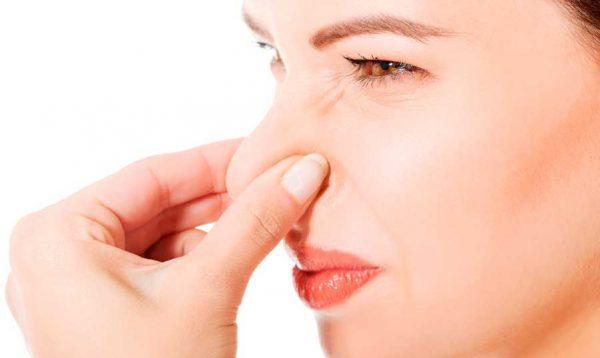 Женщина закрывает нос рукой