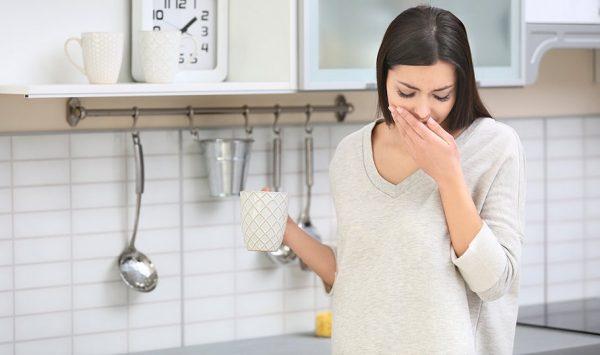 Беременная женщина стоит на кухне и закрывает рот рукой из-за отрыжки