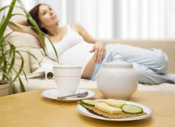 Бутерброд на столе на фоне беременной женщины