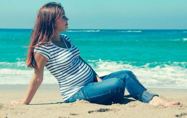 Беременная женщина сидит на берегу моря
