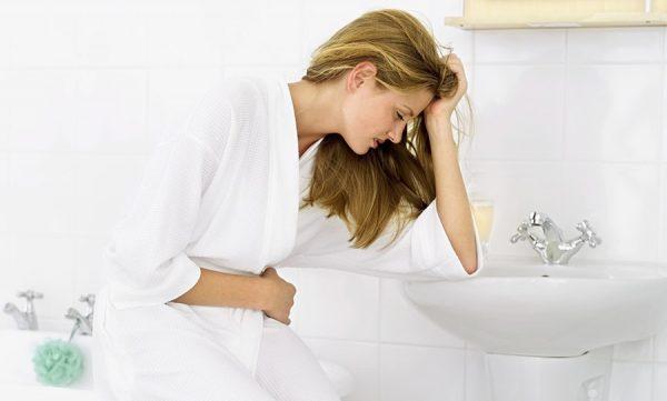 женщина держится за живот, облокотившись на умывальник