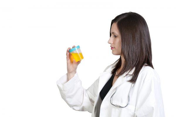 Врач держит в руке баночку для анализов