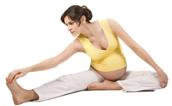 Беременная женщина делает гимнастическое упражнение