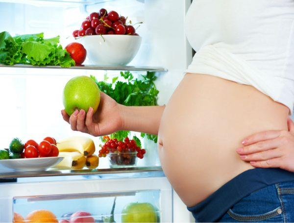 Беременная держит яблоко в руке