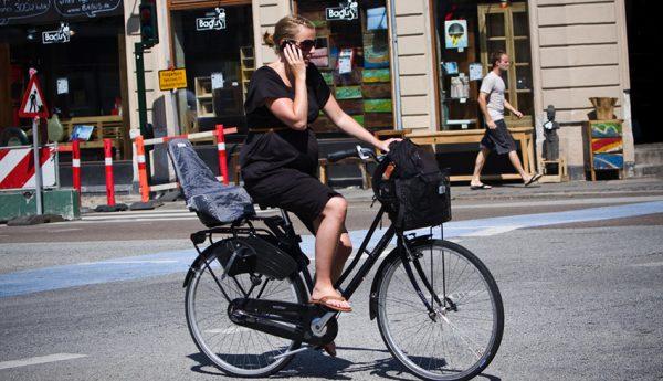 Беременная на большом сроке едет на велосипеде по улице европейской страны