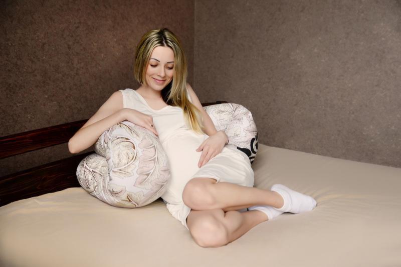 Беременная полулежит на кровати