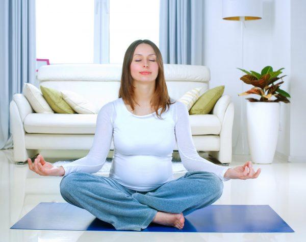 Беременная сидит в позе для йоги