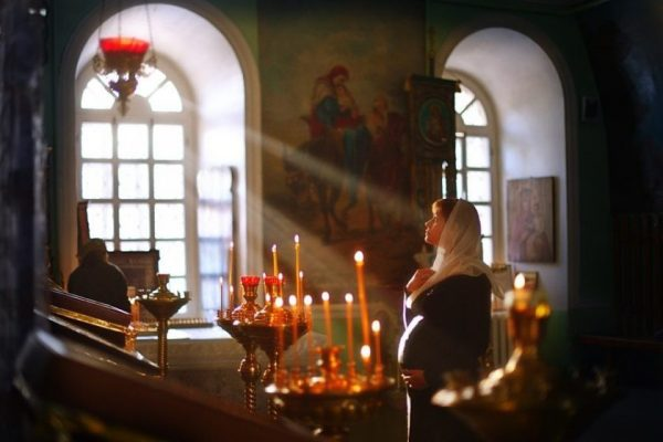 беременная женщина молится в храме Божьем