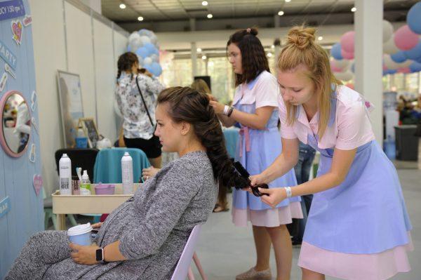 мастер в салоне укладывает волосы беременной