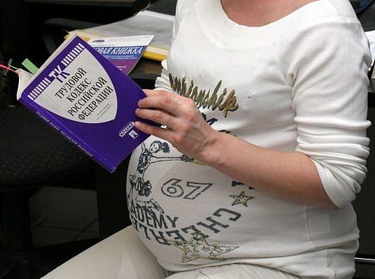 Беременная женщина читает трудовой кодекс РФ