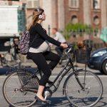 Беременная женщина едет на велосипеде с высоким рулём и вертикальной посадкой