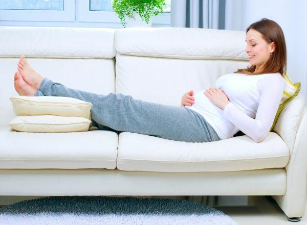 Беременная женщина лежит на диване