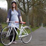Беременная женщина стоит возле велосипеда и улыбается