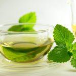 Чашка чая и листья мелиссы на столе
