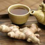 Чай с имбирём и корень имбиря рядом с заварником на столе