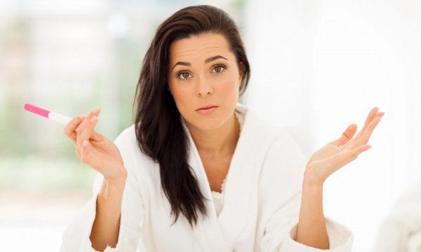 Девушка держит тест и разочарованно разводит руками