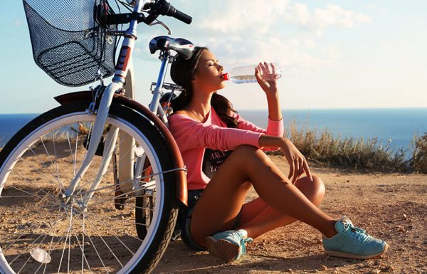 Девушка сидит возле велосипеда и пьёт воду из бутылки