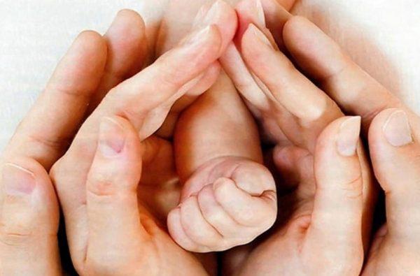 Руки женщины, мужчины и ребёнка, составляющие сердце