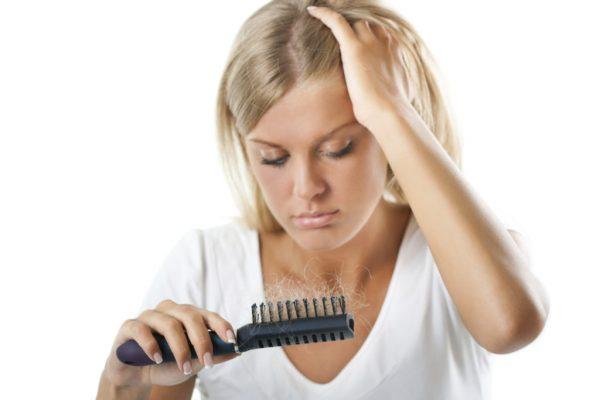 девушка смотрит на расчёску с клоками волос