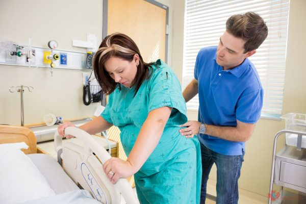 Мужчина делает массаж поясницы беременной