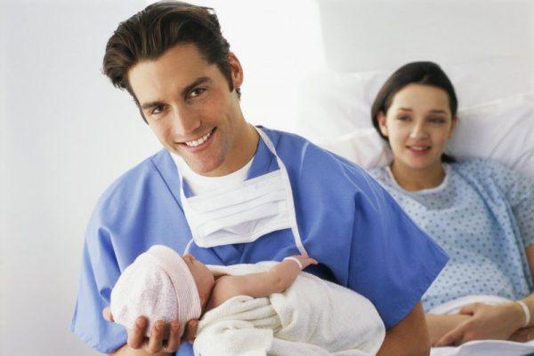 Мужчина держит ребёнка, а сзади на кровати лежит женщина
