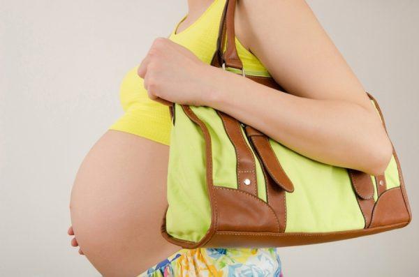 Беременная женщина с сумкой через плечо
