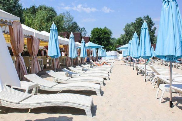 пляж с шезлонгами и зонтами от солнца