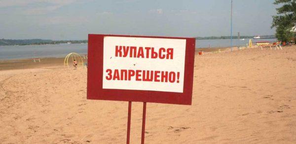 табличка «купаться запрещено» на речном пляже