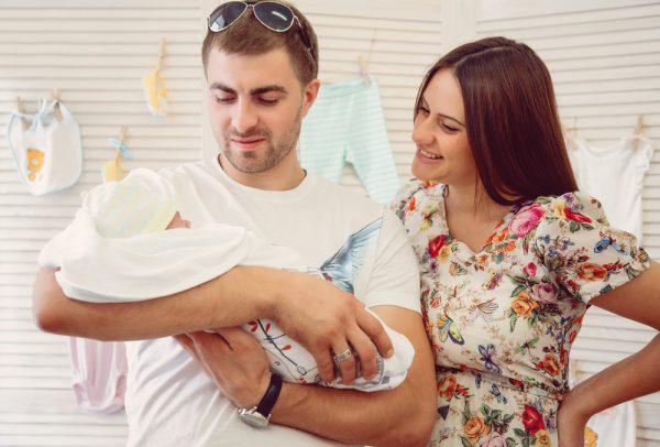 мама в платье и папа с новорождённым на руках