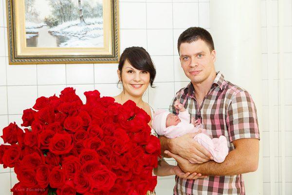мама с огромным букетом роз и папа с малышом на руках
